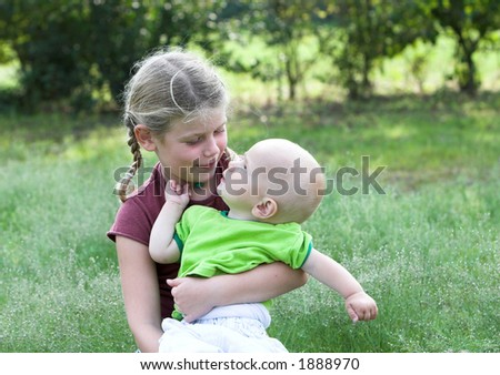 Baby boy looking up at his bigger sister with a questioning look - stock photo