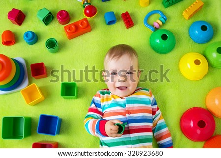 Baby boy lying on green blanket with many toys around - stock photo