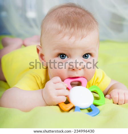 Baby boy lying on his stomach with teether in the mouth - stock photo