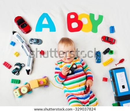 Baby boy lying on soft blanket with letters above - stock photo
