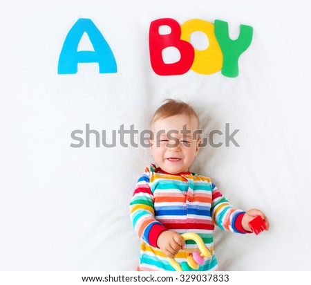 Baby boy lying on soft blanket with letters above