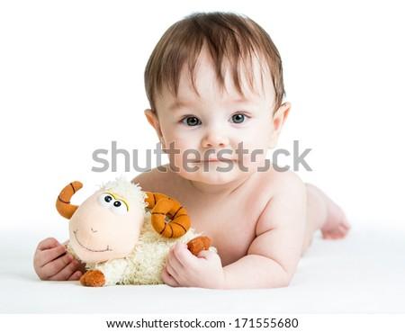 baby boy lying on tummy with lamb toy - stock photo