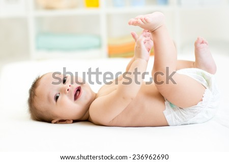 baby boy lying on white sheet and holding his legs - stock photo