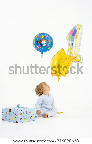 Baby boy (6-9 months) by present looking at baloons - stock photo