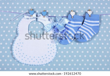 Baby boy nursery blue socks and bib, with dummy pacifier hanging from pegs on a line against a blue polka dot background for baby shower or newborn greeting card. - stock photo