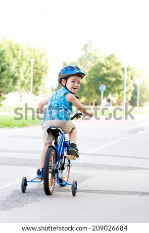 Baby boy on bike with crash helmet - stock photo