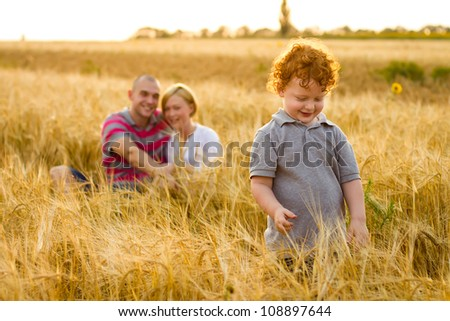 baby boy on the  foreground  and parents looking at him sitting in wheat field on background - stock photo
