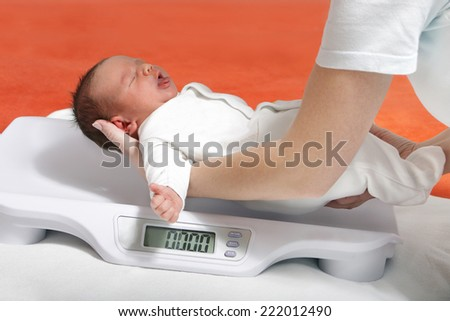 baby boy on weight scale - stock photo