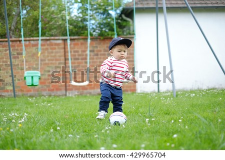 Baby boy playing a ball in the park.Selective focus. - stock photo