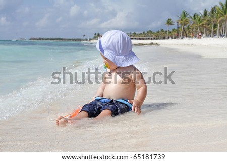 Baby boy playing in ocean waves on the beach