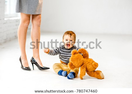Baby boy playing near the woman's beautiful legs on the white floor