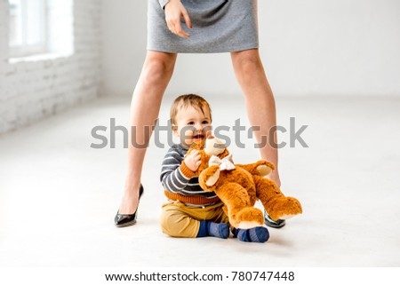 Baby boy playing near the woman's beautiful legs sitting on the white floor