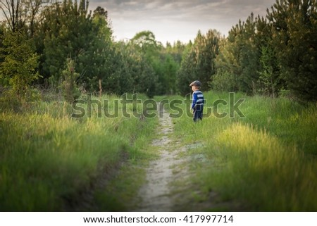 Baby boy playing on meadow at spring afternoon. Happy childhood - stock photo