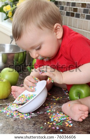 Baby boy playing on messy counter top - stock photo