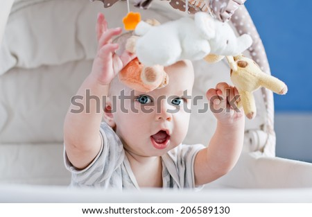 Baby boy playing sitting in the cradle with mobile toy  - stock photo