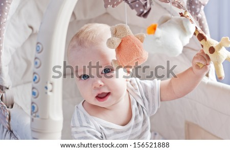 Baby boy playing sitting in the cradle with mobile toy giraffe - stock photo