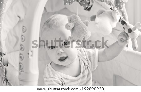 Baby boy playing sitting in the cradle with mobile toy giraffe ( black and white ) - stock photo