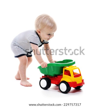 Baby boy playing toy truck. Isolated on white background