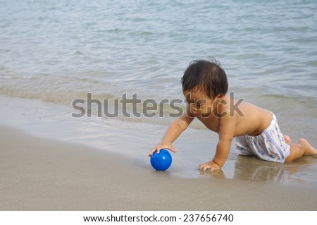 baby boy playing with a ball on the beach - stock photo