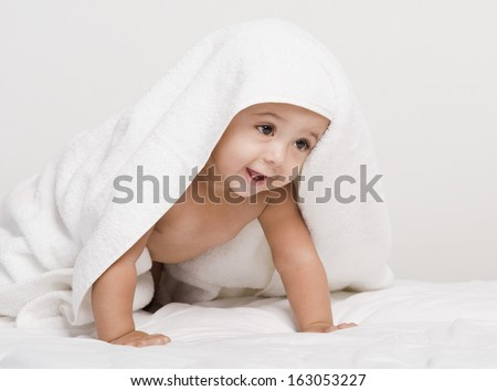 Baby boy playing with a towel