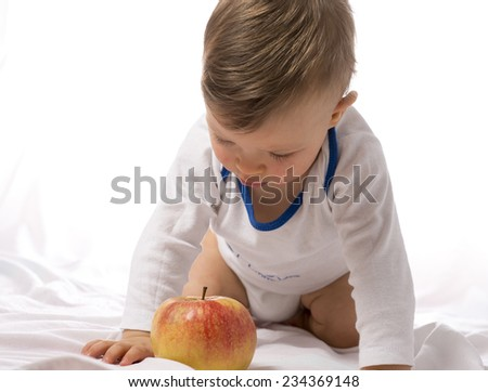 Baby boy playing with apple