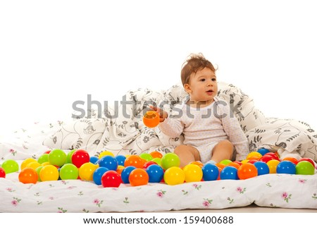 Baby boy playing with balls in bed and looking away - stock photo