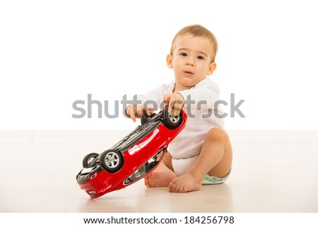 Baby boy playing with big car toy and sitting on floor in home