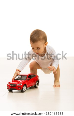 Baby boy playing with car toy home  and standing on the floor