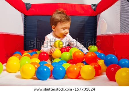 Baby boy playing with colorful balls inside playpen - stock photo