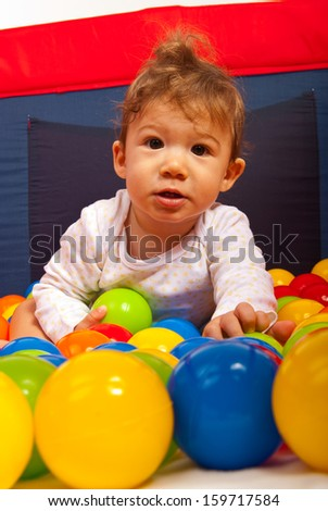 Baby boy playing with colorful ballsinside playpen - stock photo