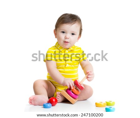 baby boy playing with colorful toy pyramid - stock photo