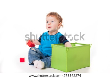Baby boy playing with colorful toys bricks, isolated on white