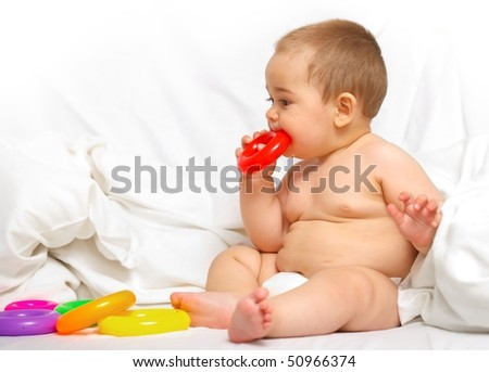 Baby boy playing with colorful toys in the bed - stock photo