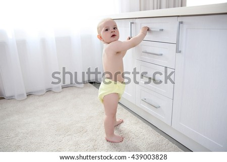 Baby boy playing with drawers in the room