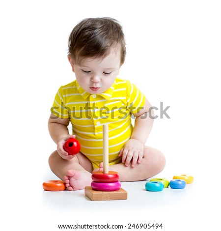 baby boy playing with educational toy pyramid isolated on white - stock photo