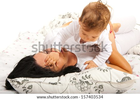 Baby boy playing with her mother face and sitting together in bed - stock photo