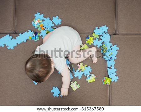 Baby boy playing with puzzle pieces on a sofa at home - stock photo