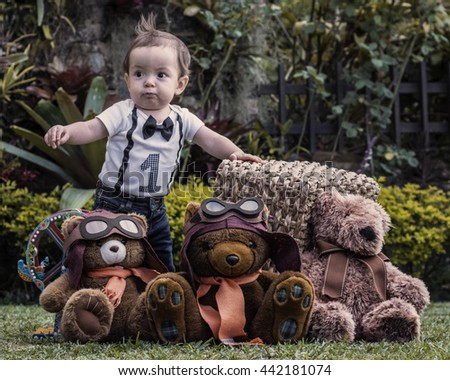 Baby boy playing with teddy bears at the garden, learning to walk - stock photo