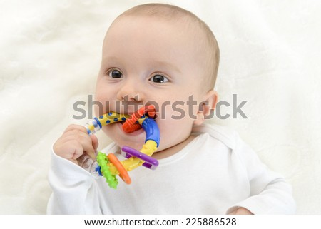Baby boy playing with teether, toy. - stock photo