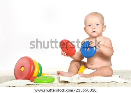 Baby boy playing with toys on a white background