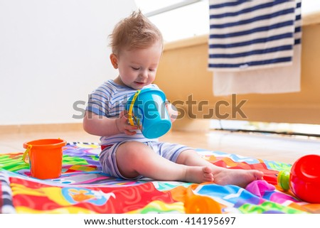 Baby boy playing with toys on the balcony