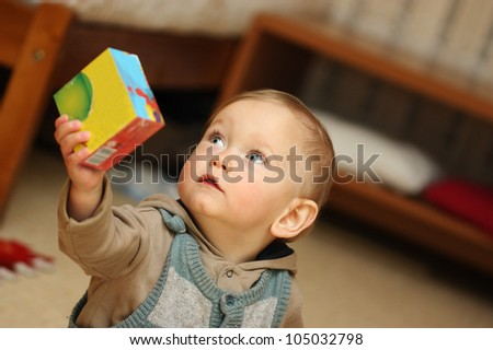 Baby Boy plays with toy in playroom - stock photo