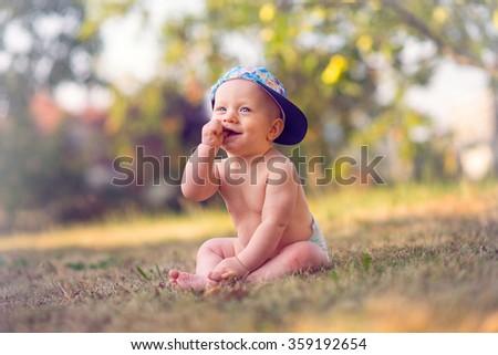 baby boy posing in a garden - stock photo