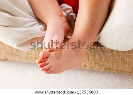Baby boy resting in a box / Detail of feet on the little baby