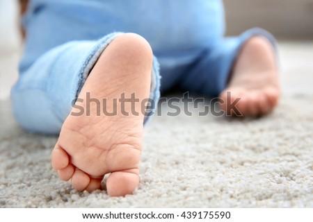 Baby boy's feet on woolen carpet, close up - stock photo