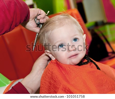 Baby boy's first haircut and he doesn't like it - stock photo