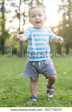 Baby boy's first steps on green grass during hot summer day - stock photo