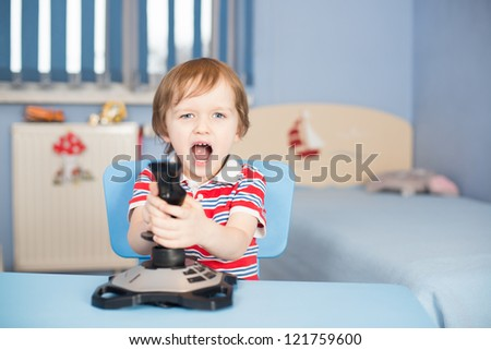 Baby boy screaming when playing computer games with joystick - stock photo