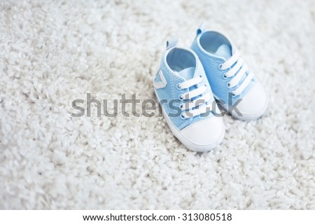 baby boy shoes blue color on fluffy background - stock photo
