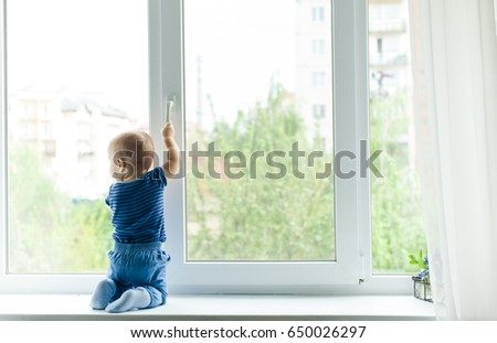Baby boy sit on the windowsill and trying to open the window pulling its handle